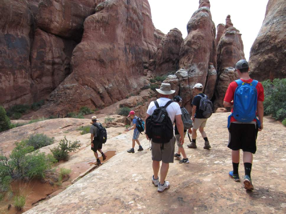 photo courtesy National Park Service  Park guide Christian Wright, left, leads Arches National Park visitors through the Fiery Furnace, one of Utah's marquee hikes limited to just 125 visitors a day. The park is proposing to eliminate commercial guiding on this coveted hike, while continuing to allow it on 23 others. Photo courtesy National Park Service.