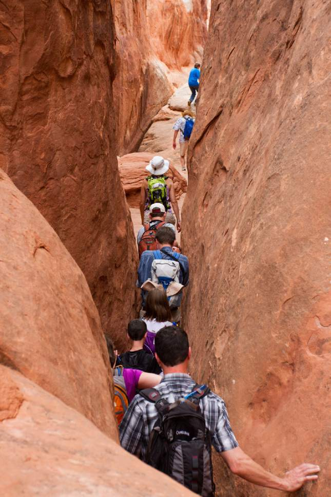 Andrew Kuhn  |  National Park Service  Led by a park guide, Arches National Park visitors scramble through the Fiery Furnace, one of Utah's marquee hikes limited to just 125 visitors a day. The park is proposing to eliminate commercial guiding on this coveted hike, while continuing to allow it on 23 others.