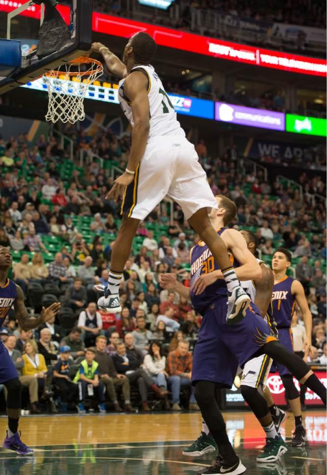 Rick Egan  |  The Salt Lake Tribune  Utah Jazz guard Alec Burks brings the crowd to their feet, as he slam dunks the ball over Phoenix Suns forward Jon Leuer (30), in NBA action Phoenix Suns vs. The Utah Jazz, in Salt Lake City, Monday, December 21, 2015.