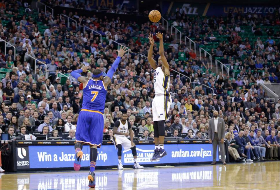 Utah Jazz guard Rodney Hood (5) shoots as New York Knicks forward Carmelo Anthony (7) defends during the second quarter of an NBA basketball game Wednesday, Dec. 9, 2015, in Salt Lake City. (AP Photo/Rick Bowmer)