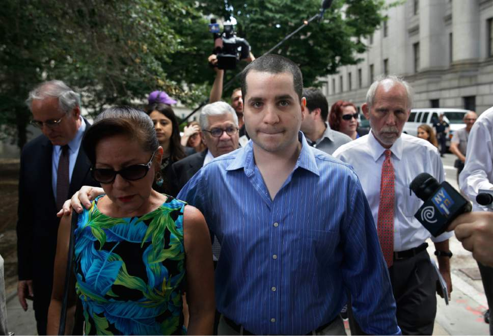 """In this Tuesday, July 1, 2014 file photo, GIlberto Valle, foreground right, leaves Manhattan federal court in New York. A federal appeals court reversed the computer-crime conviction of the ex-NYPD detective, whom tabloids dubbed the """"cannibal cop"""" for his online exchanges about kidnapping and eating women, and who improperly used a police database to gather information. Valle argued that as an officer, he was authorized to access the database. The court said the statute was ambiguous and risked criminalizing a broad array of computer use. (AP Photo/Seth Wenig)"""