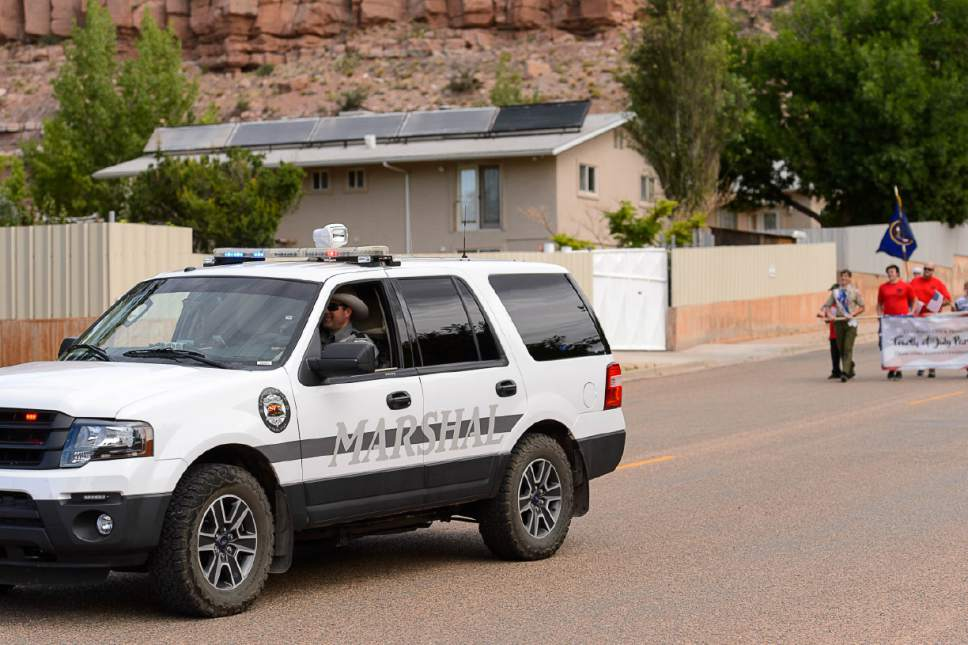 Trent Nelson  |  The Salt Lake Tribune With a wall-off compound in the background, a Colorado City Marshal vehicle leads the way as the Colorado City and Hildale Fourth of July Parade makes its way down Central Street in Hildale, UT, and Colorado City, AZ, Saturday July 2, 2016.