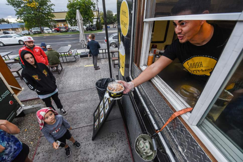 Francisco Kjolseth | The Salt Lake Tribune Daniel Arellano serves up an order from the Cupbop food truck during a recent visit to the Soho Food Park in Holladay. Food truck owners often need to navigate confusing governmental regulations from city to city. The Soho Food Park is an example of how one city has made it more convenient for food trucks to operate.