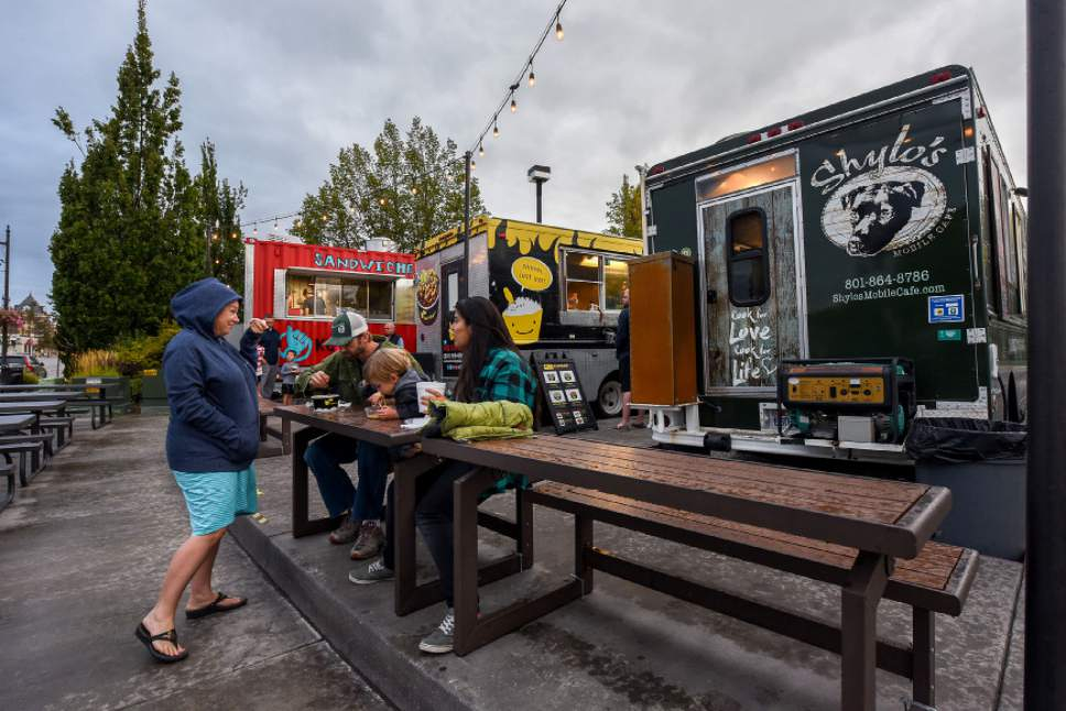 Francisco Kjolseth | The Salt Lake Tribune Diners gather recently around the regularly rotating options of six food trucks parked at the Soho Food Park in Holladay.  Food truck owners often need to navigate confusing governmental regulations from city to city. The Soho Food Park is an example of how one city has made it more convenient for food trucks to operate.