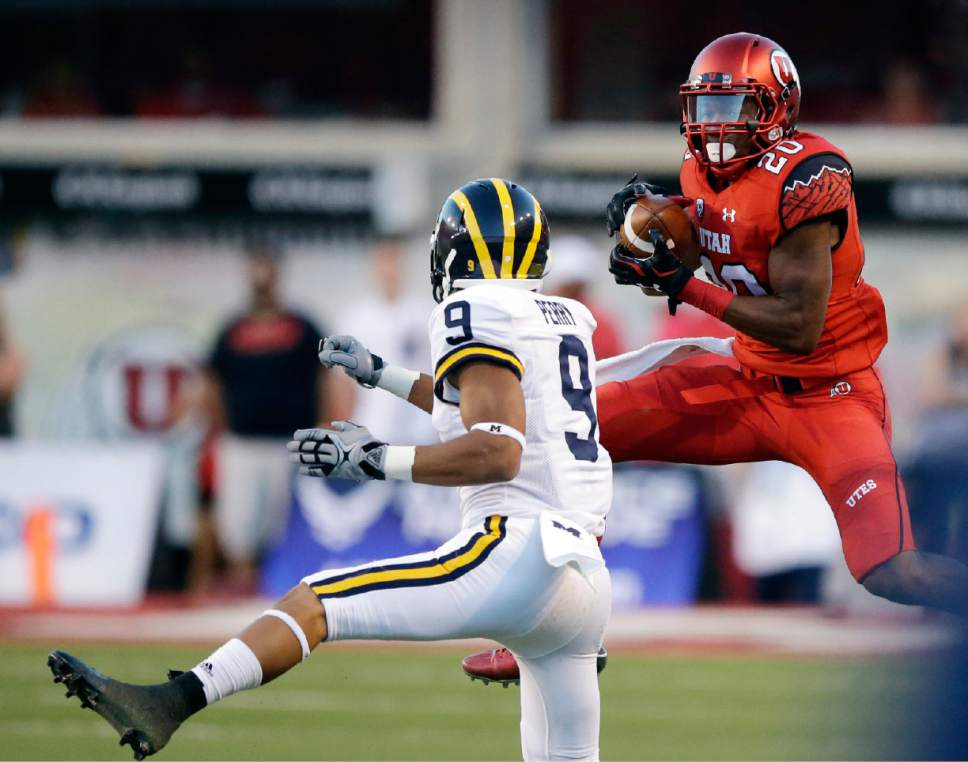 Utah defensive back Marcus Williams (20) catches an interception against Michigan wide receiver Grant Perry (9) in the second quarter during an NCAA college football game, Thursday, Sept. 3, 2015, in Salt Lake City. (AP Photo/Rick Bowmer)
