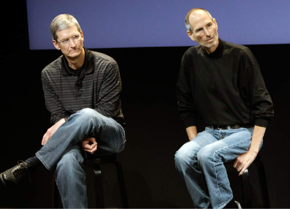 "FILE - This July 16, 2010, file photo shows Apple's Tim Cook, left, and Steve Jobs, right, during a meeting at Apple in Cupertino, Calif. Apple wants to encourage millions of iPhone owners to register as organ donors through a software update that will add an easy sign-up button to the health information app that comes installed on every smartphone the company makes. CEO Cook says he hopes the new software, set for limited release in early July 2016, will help ease a critical and longstanding donor shortage. He said the problem hit home when his friend and former boss, Apple co-founder Jobs, endured an ""excruciating"" wait for a liver transplant in 2009. (AP Photo/Paul Sakuma, File)"
