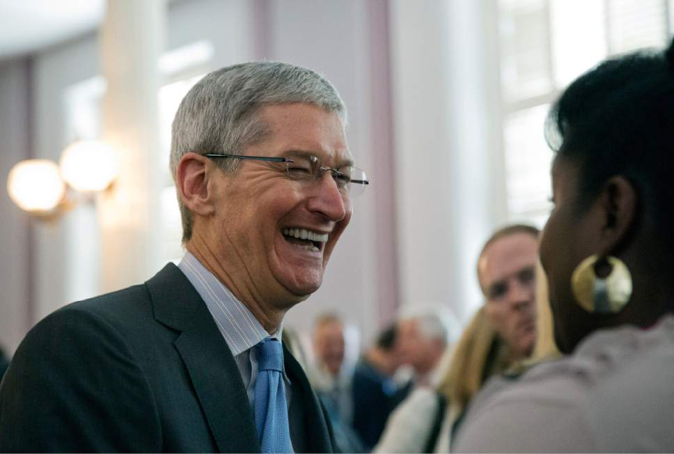 Brynn Anderson  |  AP file photo Apple CEO Tim Cook, an Alabama native, laughs with a group before an Alabama Academy of Honor ceremony at the state Capitol in Montgomery, Ala., in 2014.