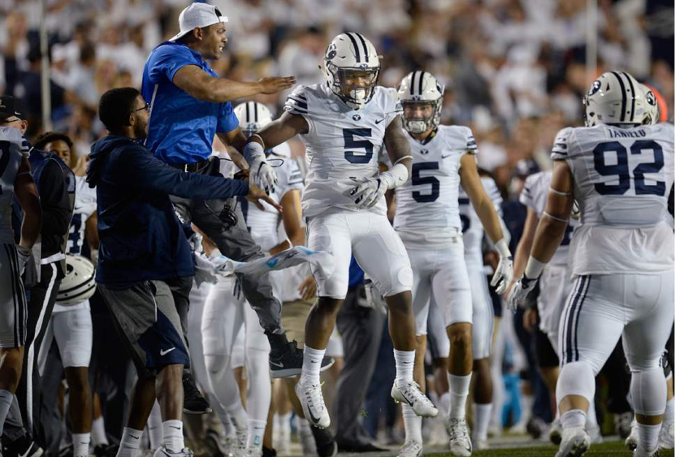 Scott Sommerdorf   |  The Salt Lake Tribune   BYU DB Dayan Lake (5) celebrates with the BYU bench after intercepting a pass and returning it to the 14 yard line to set up a TD during first half play. BYU led Toledo 21-14 at the end of the 1st quarter, Friday, September 30, 2016.