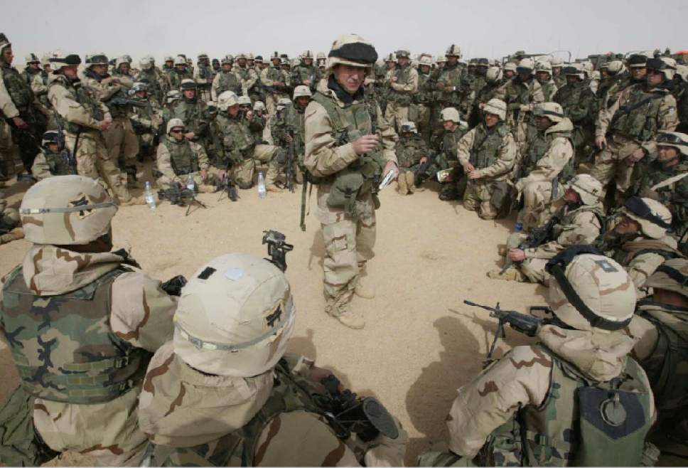U.S. Capt. Bud Ford of Clarksville, Tenn., center, briefs soldiers from the 3rd Brigade of the 101st Airborne Division in a staging areain the Kuwaiti desert Friday, March 21, 2003. Allied forces missions continue as combat units rumbled across the desert into Iraq from the south and bombed limited targets in Baghdad. (AP Photo/Jean-Marc Bouju)