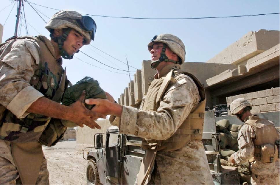 Lance Cpl. Jason Southerland, 25, of Salt Lake City, Utah, right, hands Pfc. Phillip Marquez, 21, of Coachella, Calif.,  sand bags as Marines of the Fox Company, 2nd Battalion, 1st Marine Regiment, fortify their position at a home in the northwest section of Fallujah, Iraq on Wednesday, April 14, 2004. (AP Photo/North County Times, Hayne Palmour IV)