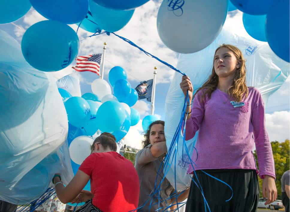 Leah Hogsten  |  The Salt Lake Tribune l-r Cottonwood Heights  youth city council members Alissa Boyack, Nicole Cunningham and Lareesa Sumsion wrangle balloons for the ceremony in the high wind. Cottonwood Heights City Hall officials, dignitaries and residents celebrated its official opening with an open house and ribbon cutting September, 29, 2016.