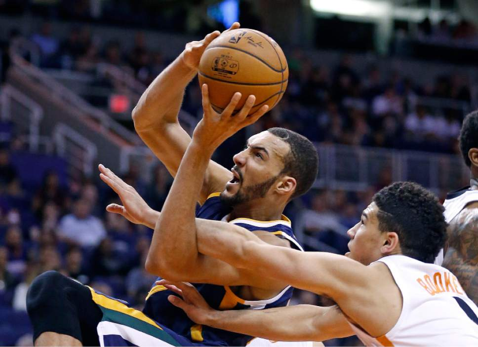 Utah Jazz's Rudy Gobert, left, gets fouled by Phoenix Suns' Devin Booker, right, during the first half of an NBA preseason basketball game Wednesday, Oct. 5, 2016, in Phoenix. (AP Photo/Ross D. Franklin)