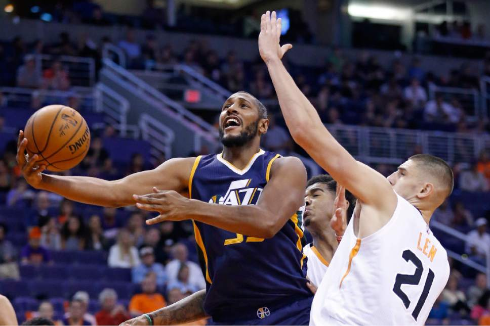 Utah Jazz's Boris Diaw, left, gets fouled as he drives past Phoenix Suns' Alex Len (21) and Marquese Chriss, second from right, during the first half of an NBA preseason basketball game Wednesday, Oct. 5, 2016, in Phoenix. (AP Photo/Ross D. Franklin)