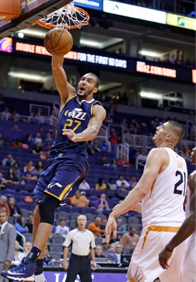 Utah Jazz's Rudy Gobert (27) dunks as he gets past Phoenix Suns' Alex Len (21) during the first half of an NBA preseason basketball game Wednesday, Oct. 5, 2016, in Phoenix. (AP Photo/Ross D. Franklin)