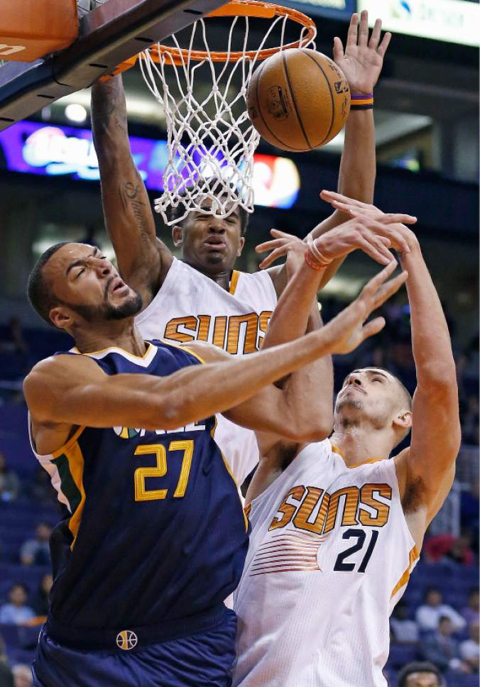 Utah Jazz's Rudy Gobert (27) battles with Phoenix Suns' Alex Len (21) and Marquese Chriss, middle, for a rebound during the first half of an NBA preseason basketball game Wednesday, Oct. 5, 2016, in Phoenix. (AP Photo/Ross D. Franklin)