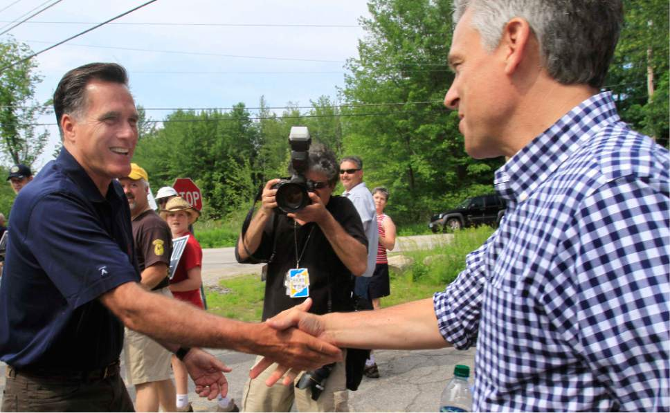Republican presidential candidate, former Massachusetts Gov. Mitt Romney, left, greets fellow candidate, former Utah Gov. Jon Huntsman, Jr., prior to the start the Fourth of July parade in Amherst, N.H., Monday, July 4, 2011. (AP Photo/Jim Cole)