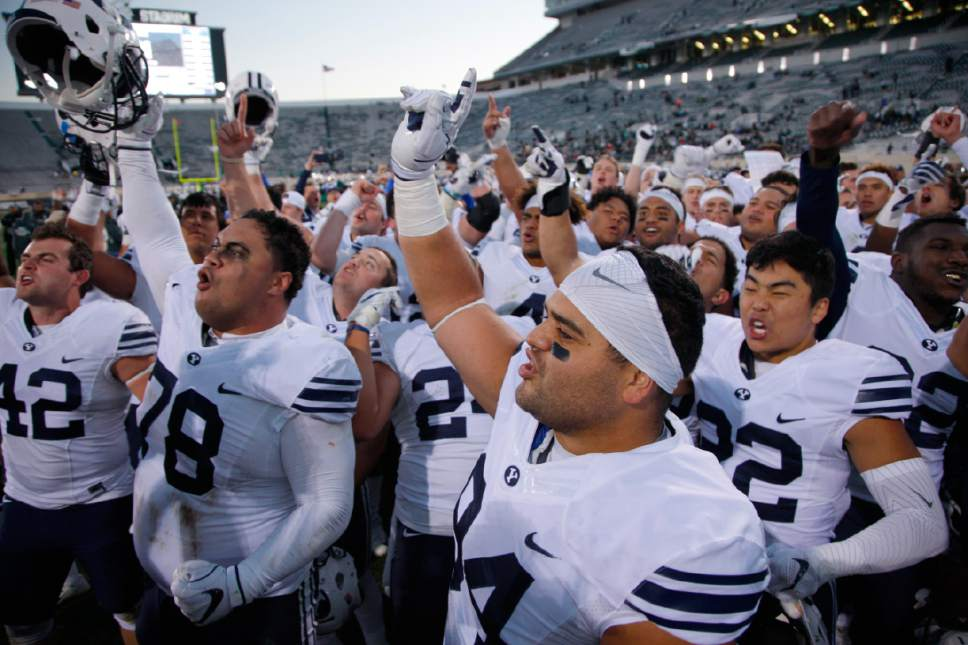 BYU players, including Austin Heder (42), Tuni Kanuch (78), Kesni Tausinga (94) and Hiva Lee, right, celebrate following a 31-14 win over Michigan State in an NCAA college football game, Saturday, Oct. 8, 2016, in East Lansing, Mich. (AP Photo/Al Goldis)