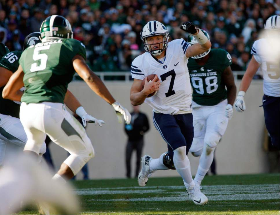 BYU quarterback Taysom Hill (7) scrambles against Michigan State's Andrew Dowell (5) during the second quarter of an NCAA college football game, Saturday, Oct. 8, 2016, in East Lansing, Mich. (AP Photo/Al Goldis)