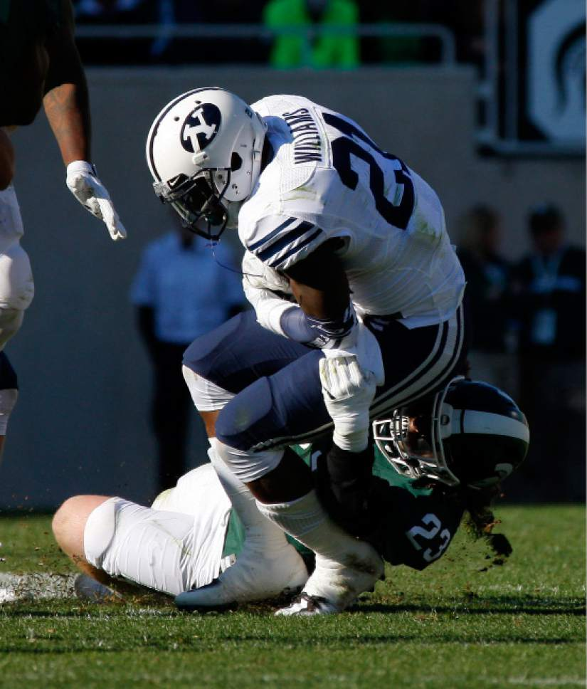 Michigan State's Chris Frey, bottom, tackles BYU's Jamaal Williams during the second quarter of an NCAA college football game, Saturday, Oct. 8, 2016, in East Lansing, Mich. (AP Photo/Al Goldis)