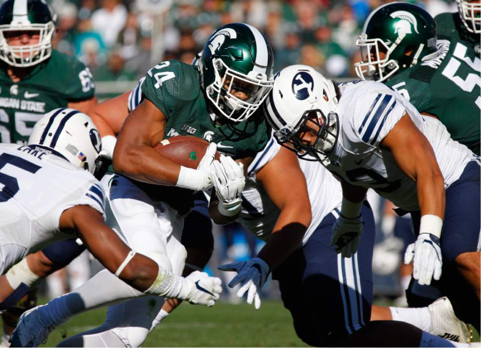 Michigan State's Gerald Holmes (24) rushes against BYU's Dayan Lake, left, and Francis Bernard, right, during the first quarter of an NCAA college football game, Saturday, Oct. 8, 2016, in East Lansing, Mich. (AP Photo/Al Goldis)
