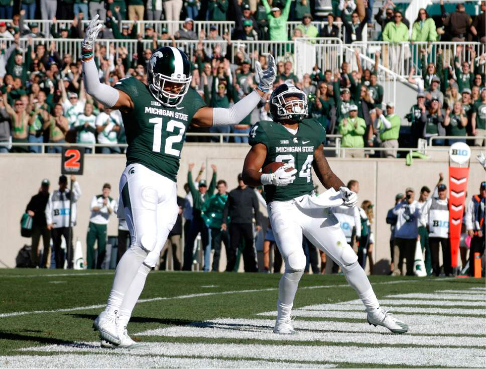 Michigan State's Gerald Holmes, right, and R.J. Shelton (12) celebrate Holmes' rushing touchdown against BYU during the first quarter of an NCAA college football game, Saturday, Oct. 8, 2016, in East Lansing, Mich. (AP Photo/Al Goldis)