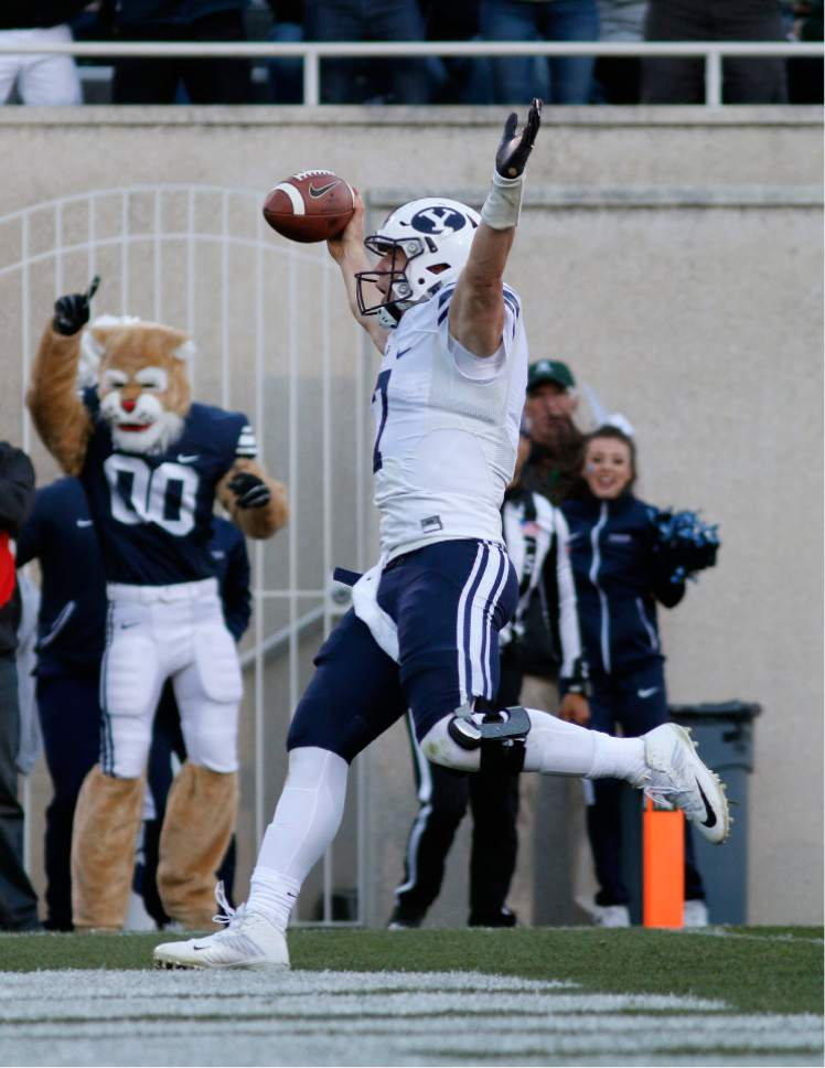BYU quarterback Taysom Hill celebrates as he scores on a keeper against Michigan State during the fourth quarter of an NCAA college football game, Saturday, Oct. 8, 2016, in East Lansing, Mich. BYU won 31-14. (AP Photo/Al Goldis)