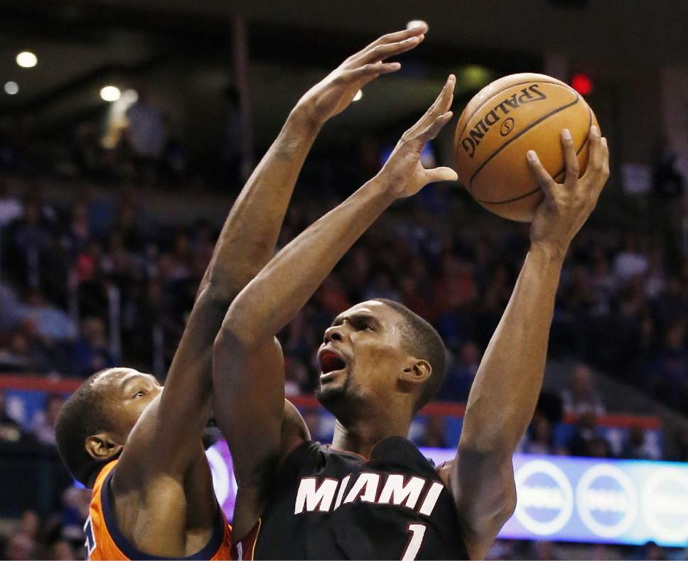 FILE - In this Jan. 17, 2016, file photo, Miami Heat forward Chris Bosh (1) shoots in front of Oklahoma City Thunder forward Kevin Durant, left, in the first quarter of an NBA basketball game in Oklahoma City. Heat President Pat Riley says the team is 'not working toward' a return for Bosh, who failed his preseason physical and is not cleared to play. (AP Photo/Sue Ogrocki, File)