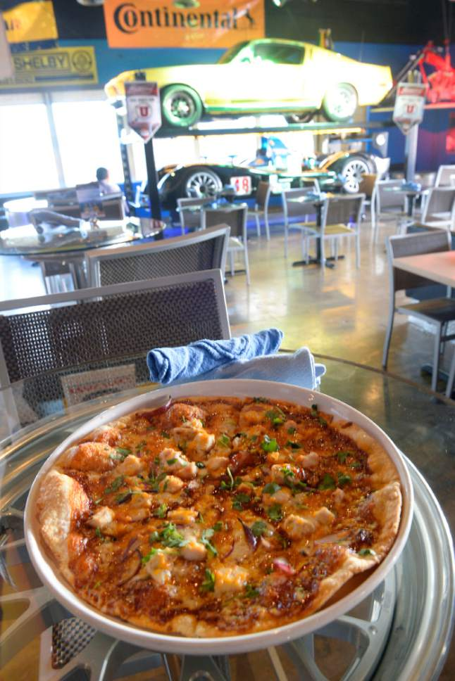 Al Hartmann  |  The Salt Lake Tribune BBQ chicken pizza at the new Garage Grill & RPM Brewery at 1122 E. Draper Parkway in Draper.  The restaurant features a car-themed interior with race cars and classic hot rods.