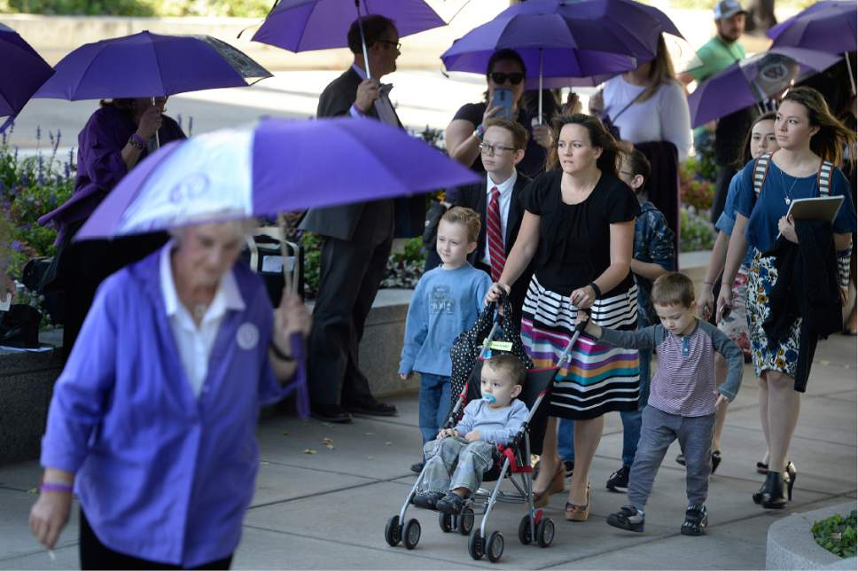 Scott Sommerdorf   |  The Salt Lake Tribune   A woman walking with seven children walks past the Ordain Women group who were queued up outside the LDS Church Administration Building in order to request a meeting with a general authority, Saturday, October 1, 2016.