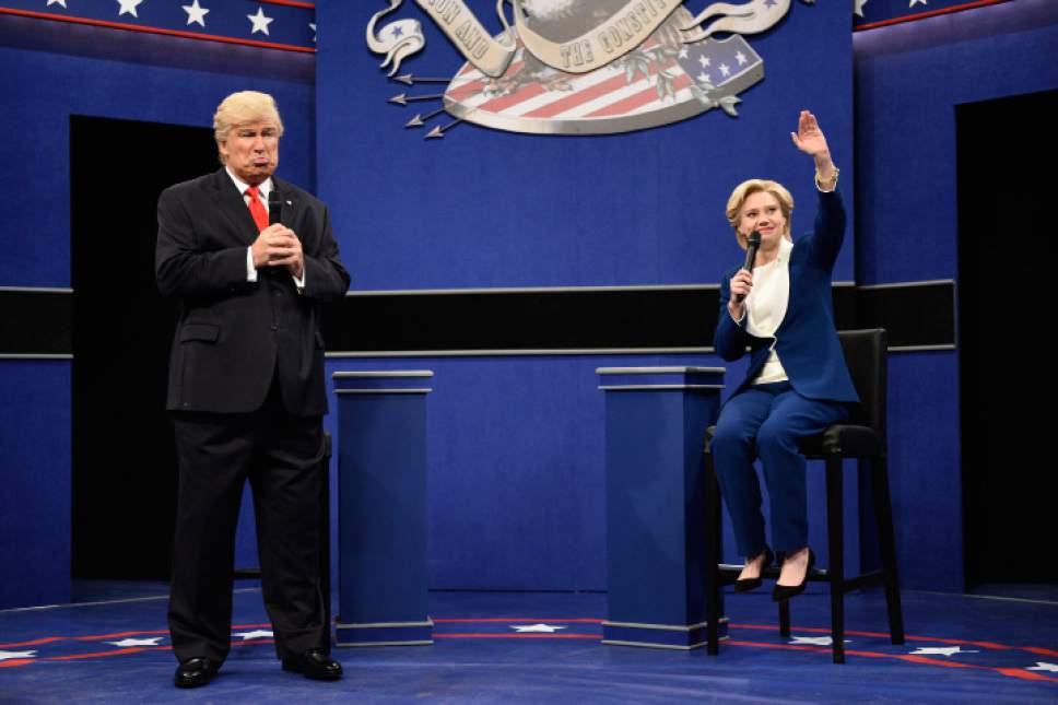"""In this Oct. 15, 2016 photo provided by NBC, Alec Baldwin, left, as Republican presidential candidate, Donald Trump, and Kate McKinnon, as Democratic presidential candidate, Hillary Clinton, perform during the during the """"Debate Cold Open"""" sketch. Republican presidential candidate Donald Trump tweeted early Sunday morning, Oct. 16 that the show's skit depicting him this week was a """"hit job."""" Trump went on to write that it's """"time to retire"""" the show, calling it """"boring and unfunny"""" and adding that Alec Baldwin's portrayal of him """"stinks.""""(Will Heath/NBC via AP)"""