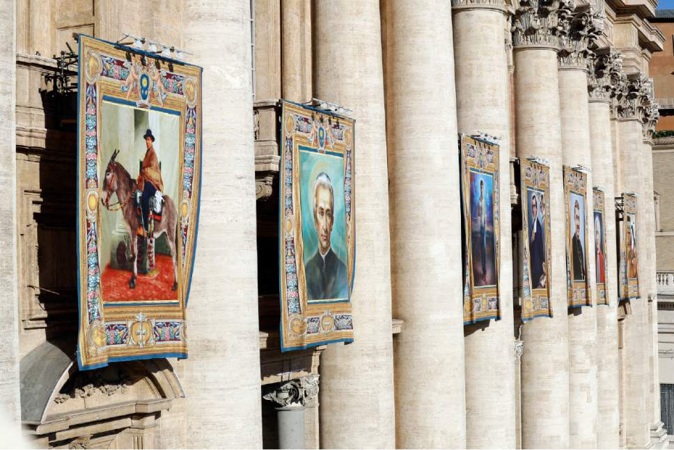 The tapestries of seven new saints, from left; Jose Gabriel del Rosario Brochero, Ludovico Pavoni, Jose Sanchez del Rio, Salomone Leclerc, Manuel Gonzalez Garcia, Alfonso Maria Fusco and Elisabetta Della Santissima Trinita' Catez, hang from the facade of St, Peter's Basilica prior to the start of a Canonization Mass celebrated by Pope Francis in St. Peter's Square, at the Vatican, Sunday, Oct. 16, 2016. (AP Photo/Andrew Medichini)