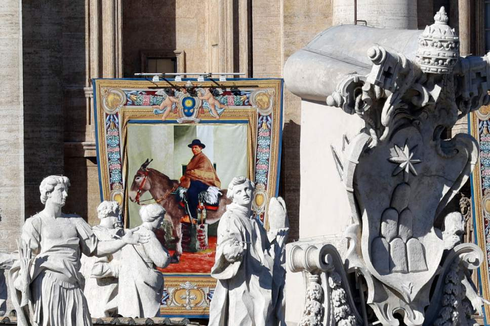 "The tapestry of Argentina's ""gaucho priest"" Jose Gabriel del Rosario Brochero hangs from the facade of St, Peter's Basilica prior to the start of a Canonization Mass celebrated by Pope Francis in St. Peter's Square, at the Vatican, Sunday, Oct. 16, 2016. The pope canonized Brochero on Sunday along with six others in one of the final big Masses of his Holy Year of Mercy. (AP Photo/Andrew Medichini)"