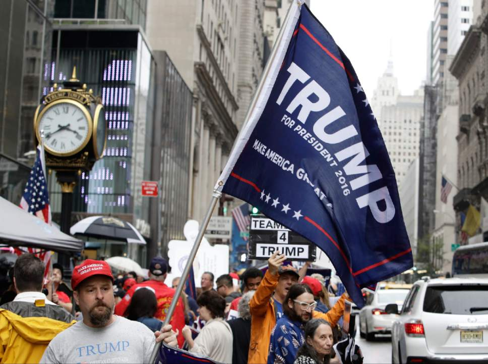 """Supporters of Republican presidential nominee Donald Trump gather at Trump Tower Saturday, Oct. 8, 2016, in New York. Trump insisted he would """"never"""" abandon his White House bid, facing an intensifying backlash from Republican leaders across the nation who called on him to quit the race following the release of his sexually charged comments caught on tape. (AP Photo/Frank Franklin II)"""