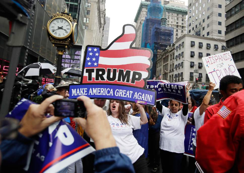 """Supporters of Republican presidential nominee Donald Trump gather at Trump Tower Saturday, Oct. 8, 2016, in New York. Trump insisted Saturday, Oct. 8, 2016, he would """"never"""" abandon his White House bid, facing an intensifying backlash from Republican leaders across the nation who called on him to quit the race following the release of his sexually charged comments caught on tape. (AP Photo/Frank Franklin II)"""