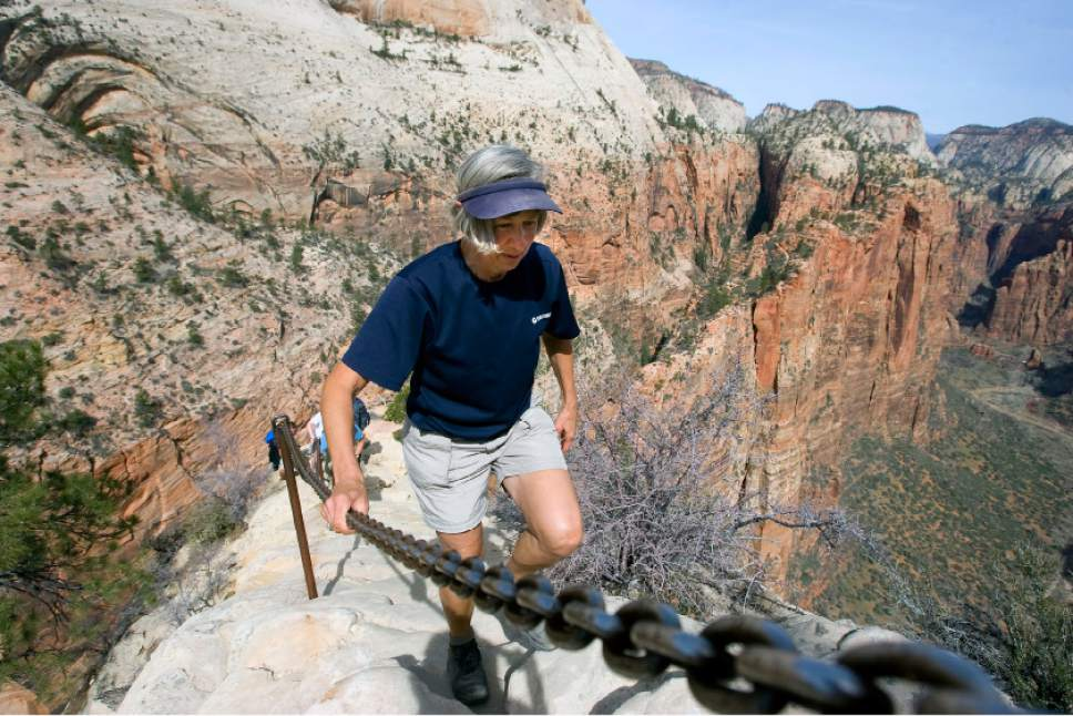 Al Hartmann  |  Tribune file photo  A hiker carefully makes her way up the Angels Landing Trail in Zion National Park in March 2009. The trail is one of the premier hikes in the park, taking visitors up a steep rock spine that climbs to a magnificent view of the Virgin River and Zion Canyon below.  The hike is not for those who fear heights. An anchor chain is embedded in the rock in steep places along the trail for hikers to grab onto for safety, but the path is steep dangerous.