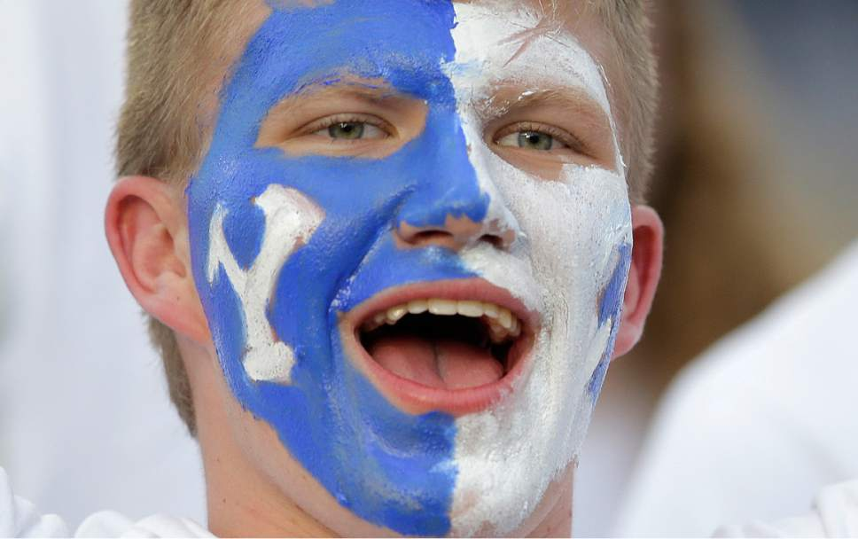 FILE - This Sept. 17, 2016, file photo, a BYU fans shouts before an NCAA college football game against UCLA, in Provo, Utah. Some of Utah's most influential Mormons, including Mitt Romney, Gov. Gary Herbert and the president of the Utah Jazz, are lobbying to get the private, Mormon church-owned Brigham Young University an invitation to join the lucrative Big 12 athletic conference. (AP Photo/Rick Bowmer, File )