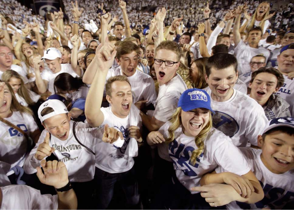 FILE _ This Sept. 12, 2015, file photo, BYU fans celebrate their victory over Boise State in an NCAA college football game in Provo, Utah. Some of Utah's most influential Mormons, including Mitt Romney, Gov. Gary Herbert and the president of the Utah Jazz, are lobbying to get the private, Mormon church-owned Brigham Young University an invitation to join the lucrative Big 12 athletic conference. (AP Photo/Rick Bowmer, File )