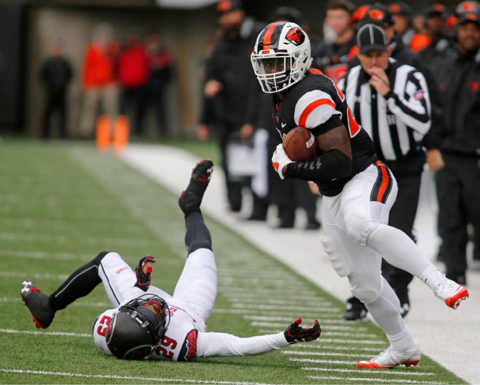 Oregon State running back Tim Cook, right, stays in bounds after avoiding a tackle by Utah's Reggie Porter in the second half of an NCAA college football game in Corvallis, Ore., on Saturday, Oct. 15, 2016. Utah won 19-14. (AP Photo/Timothy J. Gonzalez)