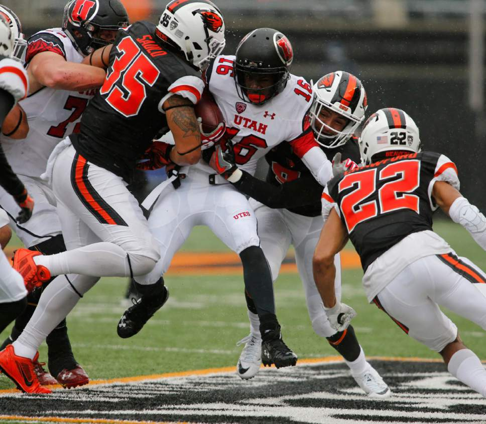 Utah's Cory Butler-Byrd (16) tries to push past Oregon State's Caleb Saulo (35) and Xavier Crawford (12) during the first half of an NCAA college football game in Corvallis, Ore., on Saturday, Oct. 15, 2016. (AP Photo/Timothy J. Gonzalez)