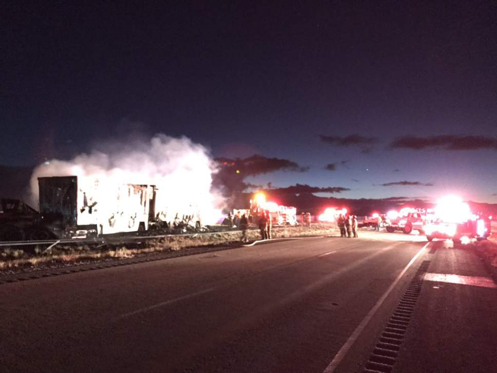 Courtesy of North Tooele Fire District  Firefighters douse a post-collision blaze early Wednesday morning on I-80. Two drivers died in the collision of one semi with the wreckage of another.