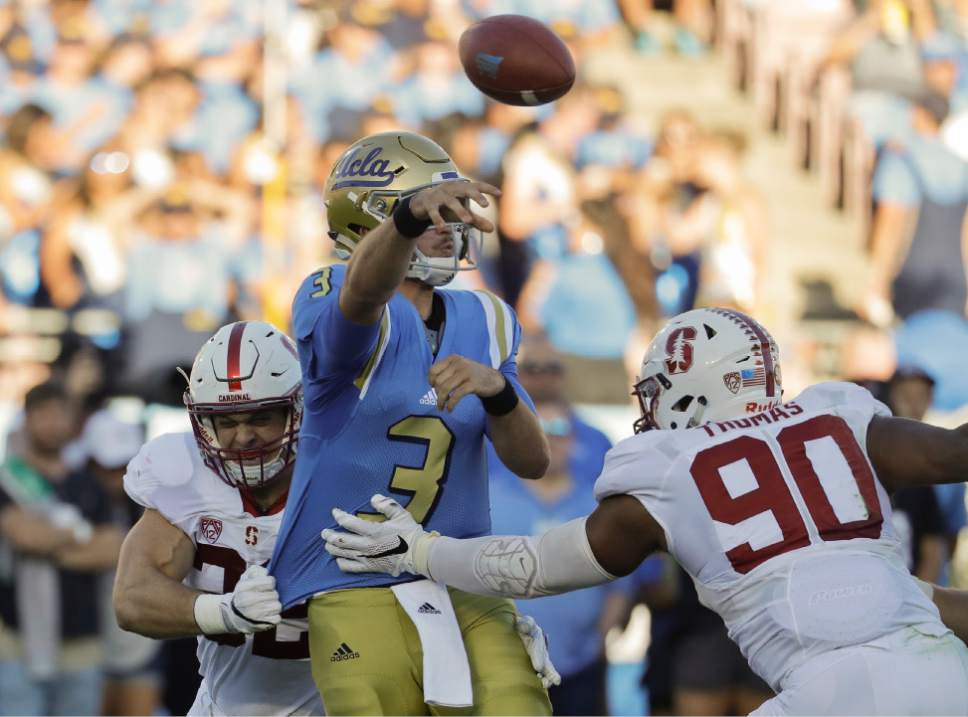 UCLA quarterback Josh Rosen, middle, throws under pressure by Stanford linebacker Joey Alfieri, left, and defensive end Solomon Thomas during the first half of an NCAA college football game in Pasadena, Calif., Saturday, Sept. 24, 2016. (AP Photo/Chris Carlson)