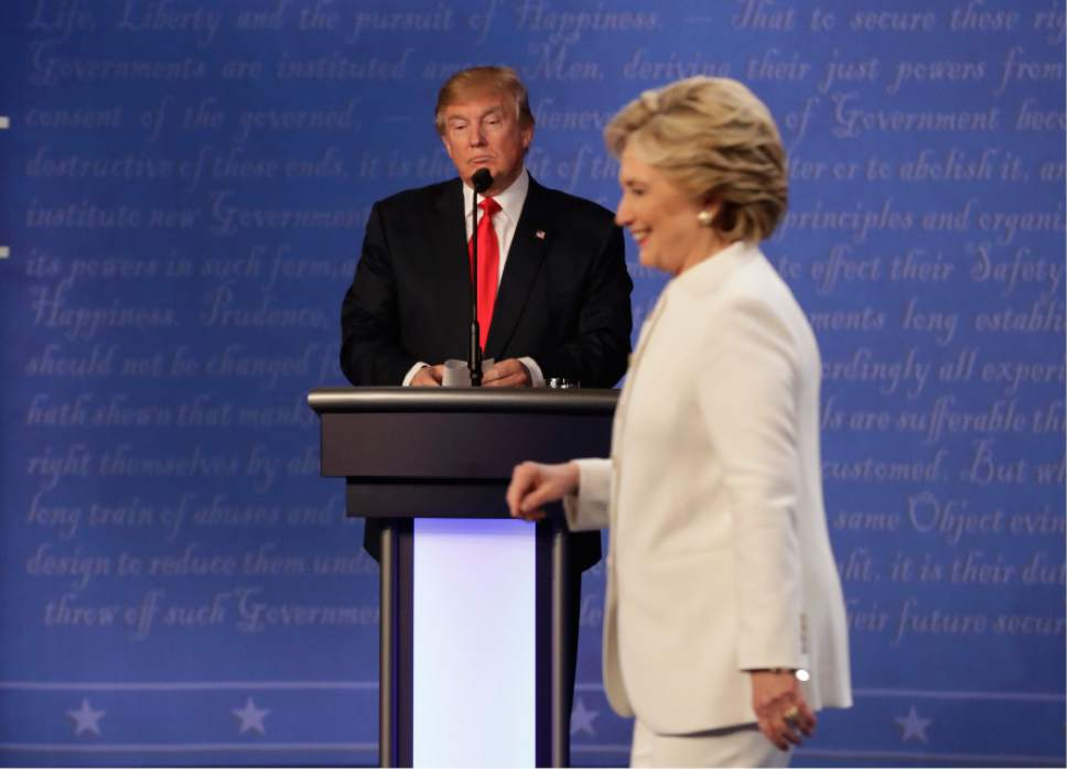 Republican presidential nominee Donald Trump waits behind his podium as Democratic presidential nominee Hillary Clinton makes her way off the stage following the third presidential debate at UNLV in Las Vegas, Wednesday, Oct. 19, 2016. (AP Photo/David Goldman)