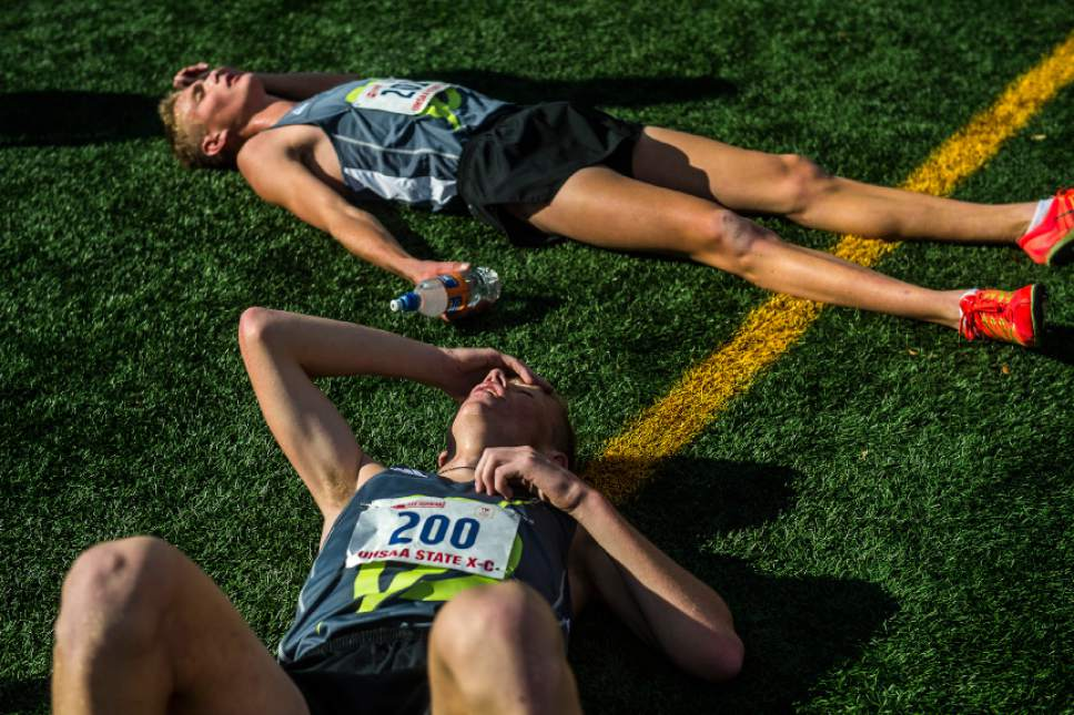 Chris Detrick  |  The Salt Lake Tribune Davis High School's Devin Jaster (200) and Josh Peters (201) rest on the ground after finishing the UHSAA State Cross Country Championships at Highland High School Wednesday October 19, 2016.