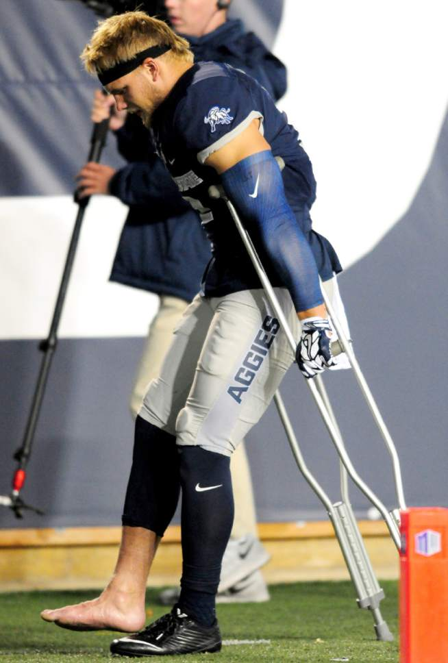 Utah State's Dallin Leavitt leaves the field on crutches during an NCAA college football game against Air Force, Saturday, Sept. 24, 2016, in Logan, Utah. (John Zsiray/Herald Journal via AP)