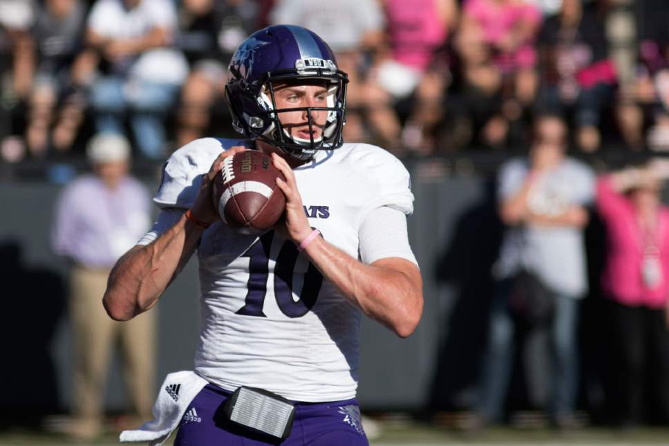 Weber State quarterback Jadrian Clark (10) looks downfield to pass against Montana in the second half of an NCAA college football game Saturday, Oct. 10, 2015, in Missoula, Mont. Weber State defeated Montana 24-21 in overtime. (AP Photo/Patrick Record)