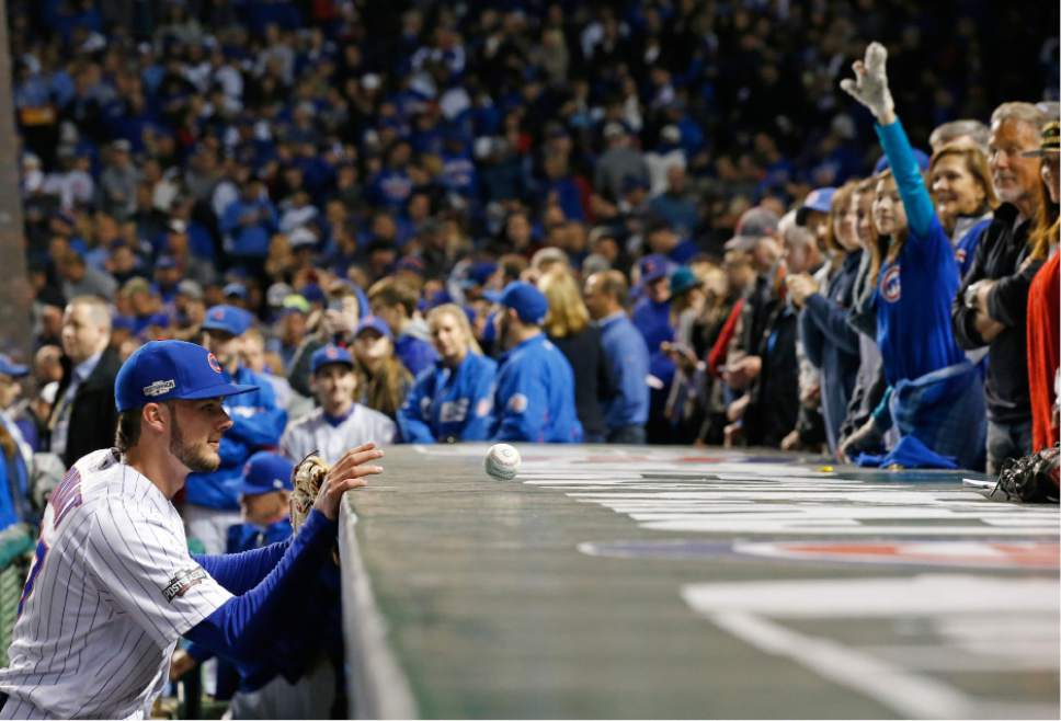 Chicago Cubs third baseman Kris Bryant (17) tosses a ball to a fan before Game 6 of the National League baseball championship series against the Los Angeles Dodgers, Saturday, Oct. 22, 2016, in Chicago. (AP Photo/Nam Y. Huh)