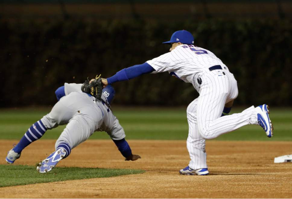 Chicago Cubs second baseman Javier Baez (9) tags it Los Angeles Dodgers left fielder Andrew Toles (60) during the first inning of Game 6 of the National League baseball championship series Saturday, Oct. 22, 2016, in Chicago. (AP Photo/David J. Phillip)