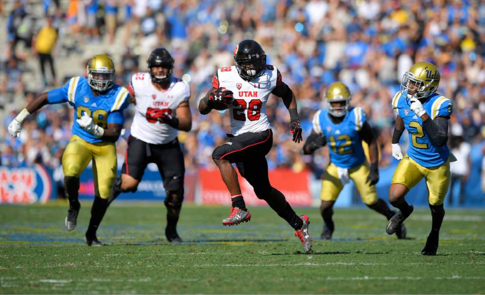Utah running back Joe Williams, center, runs for a touchdown as UCLA defensive lineman Takkarist McKinley, left, linebacker Jayon Brown, second from left, and defensive back Jaleel Wadood, right, give chase along with Utah offensive tackle Sam Tevi during the first half of an NCAA college football game, Saturday, Oct. 22, 2016, in Pasadena, Calif. (AP Photo/Mark J. Terrill)