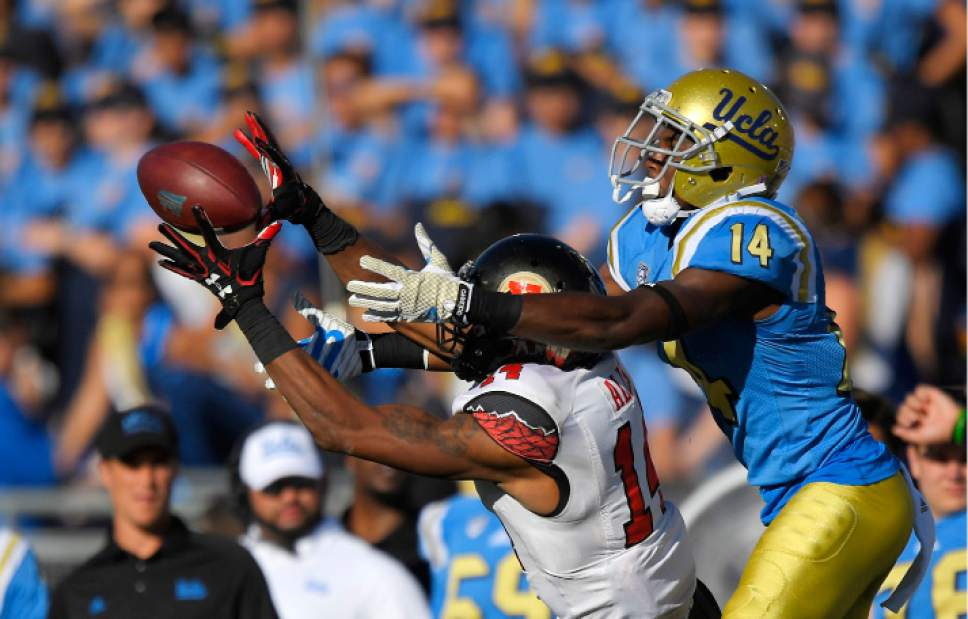 Utah defensive back Brian Allen, left, intercepts a pass intended for UCLA wide receiver Theo Howard during the second half of an NCAA college football game, Saturday, Oct. 22, 2016, in Pasadena, Calif. Utah won 52-45. (AP Photo/Mark J. Terrill)