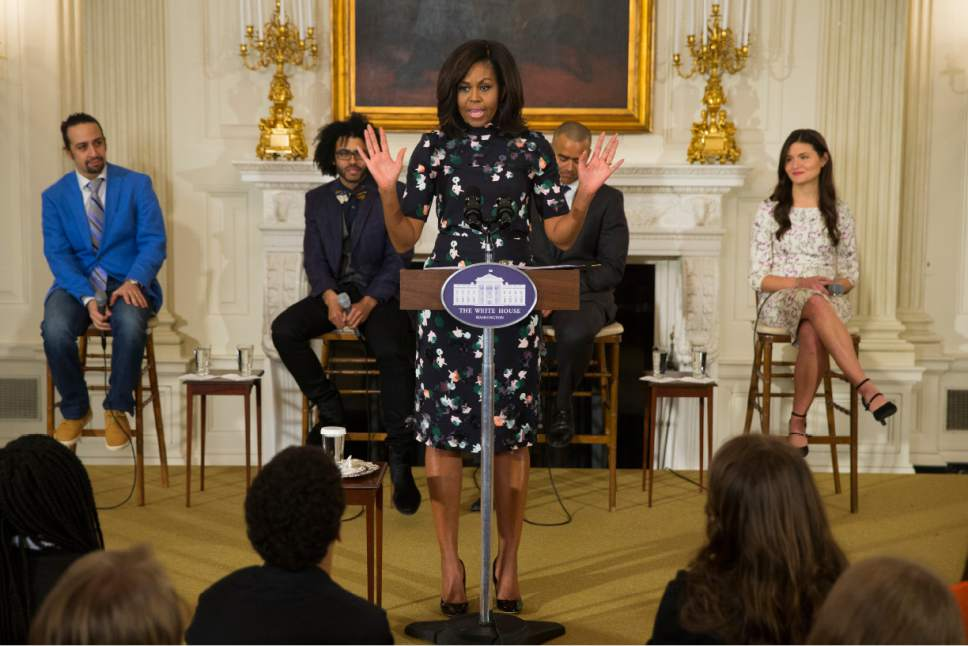 "First lady Michelle Obama speaks during an event with the cast of the Broadway play ""Hamilton"" in the State Dining Room of the White House, on Monday, March 14, 2016, in Washington. From left, actor Lin-Manuel Miranda, actor Daveed Diggs, Obama, and actor Christopher Jackson, and actress Phillipa Soo. (AP Photo/Evan Vucci)"